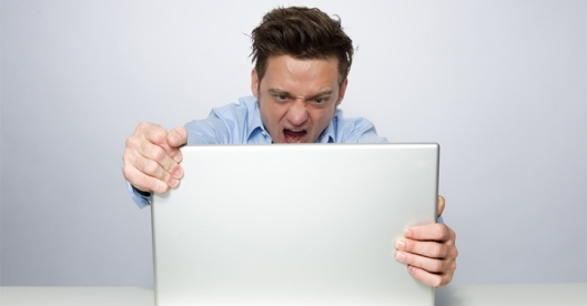 Angry man behind laptop
